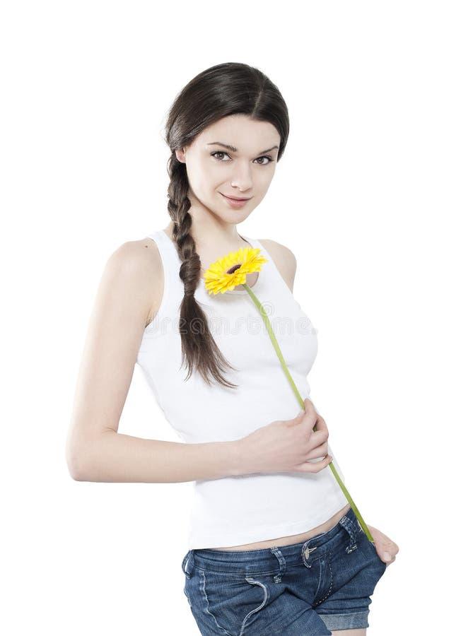 Schöne junge Brunettefrau mit gelbem gerber stockfotografie