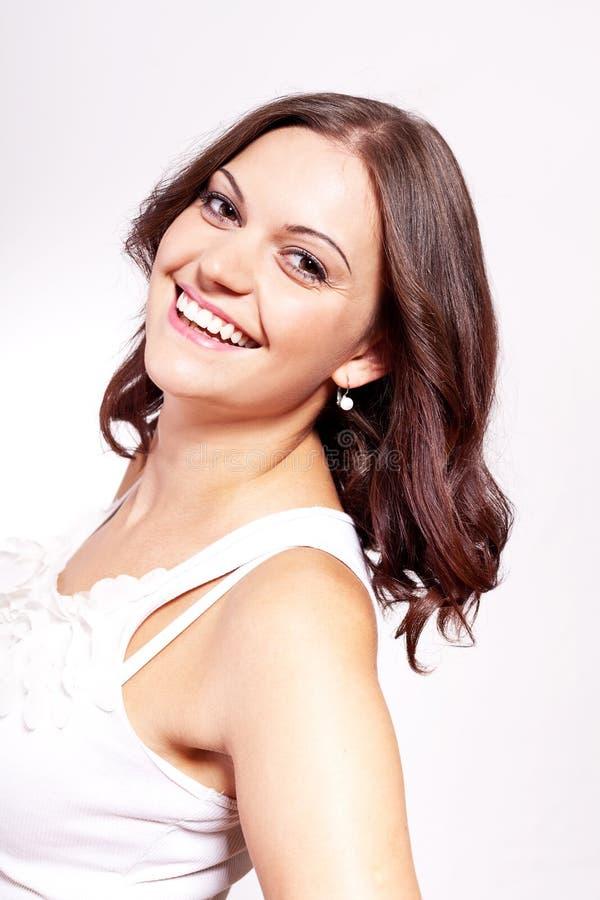 Schöne junge Brunettefrau mit großem Lächeln lizenzfreies stockbild