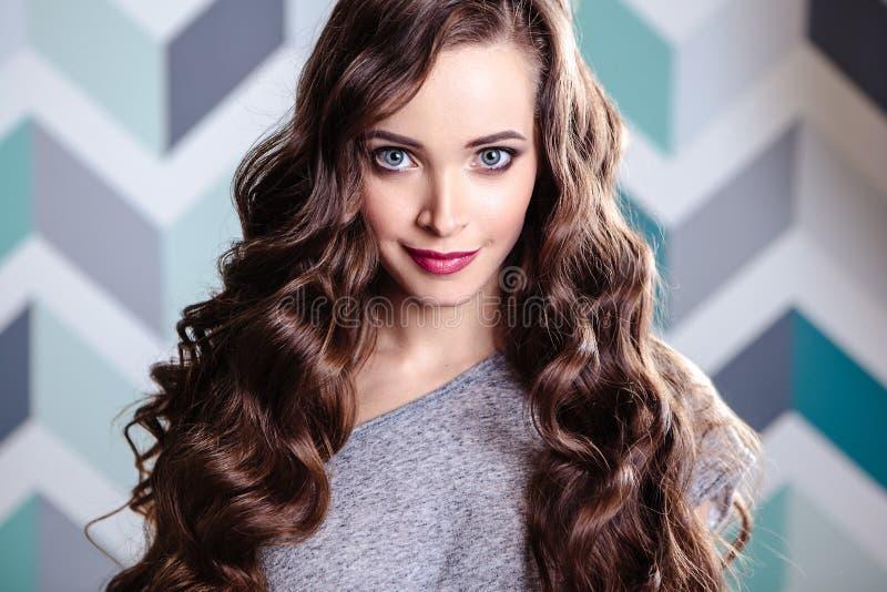 Schöne junge Brunettefrau mit langem gelocktes Haar- und Abendmake-up, Modeschönheitsporträt stockbilder