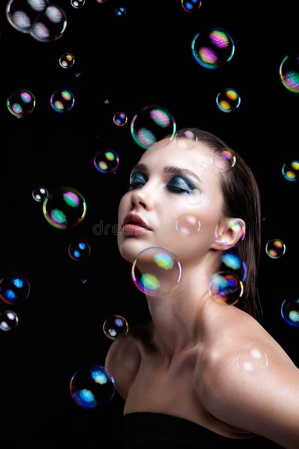 Schöne junge Brunettefrau mit Seifenblasen auf schwarzem backgr lizenzfreies stockbild