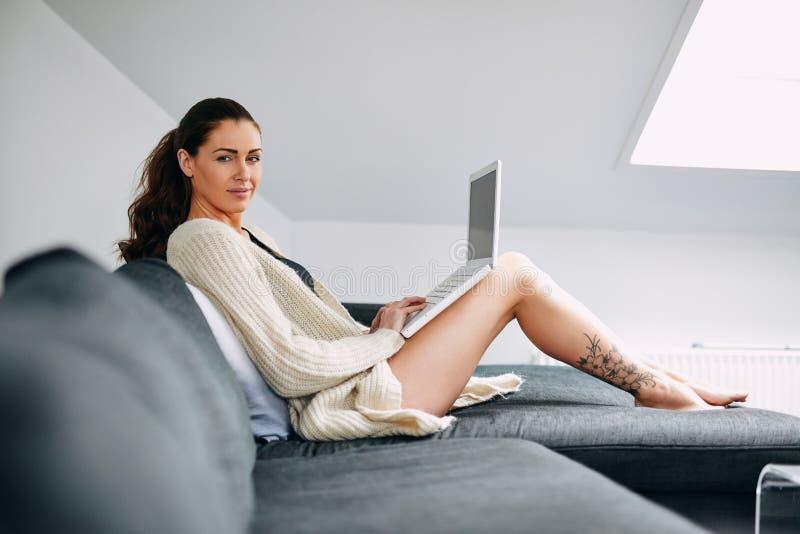 Schöne junge Dame auf Sofa mit einem Laptop lizenzfreies stockfoto