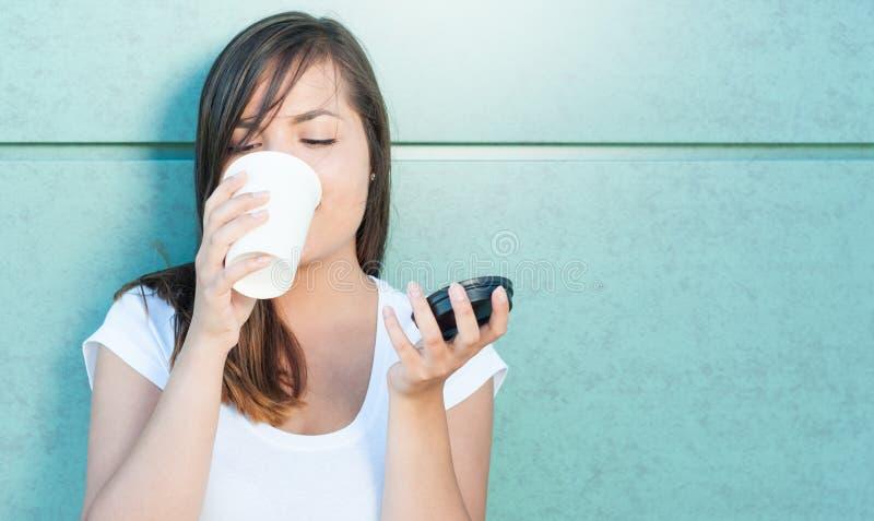 Schöne junge Dame, die das Kaffeetasse und Trinken hält stockfotos