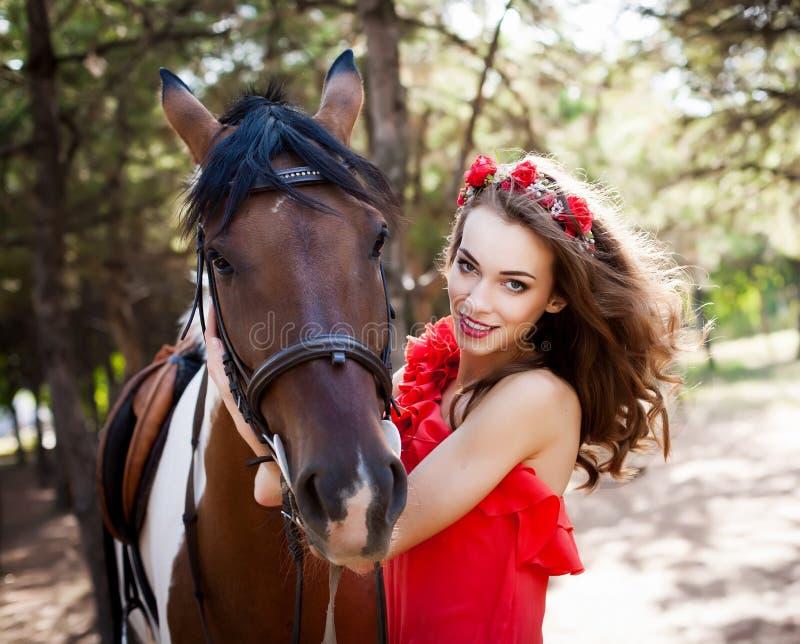 Schöne junge Dame, die das rote Kleid reitet ein Pferd am sonnigen Sommertag trägt Brunette mit dem langen gelockten Haar mit Blu stockfotos