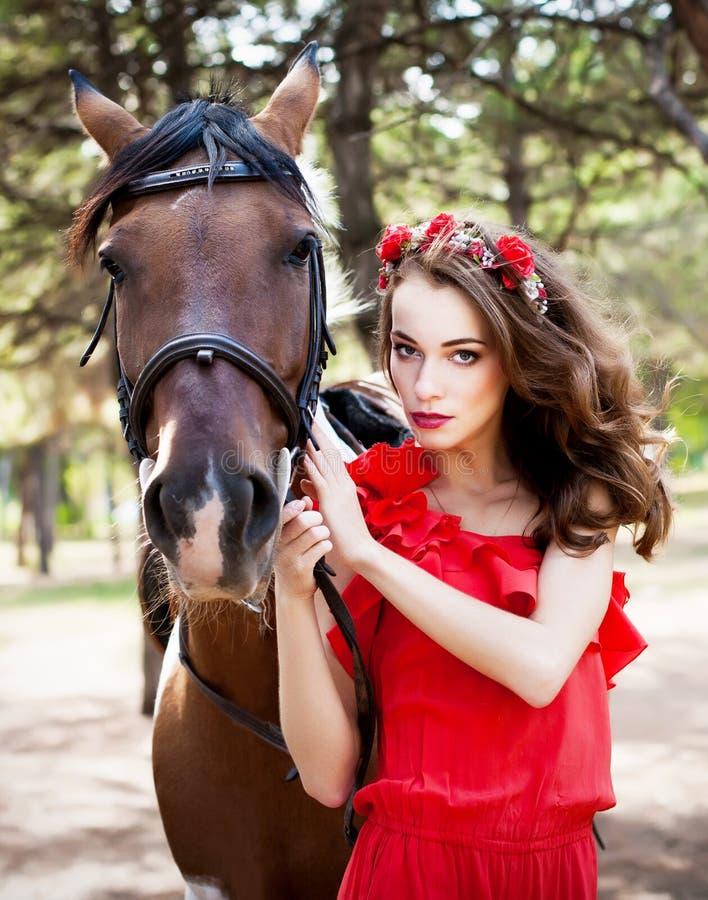 Schöne junge Dame, die das rote Kleid reitet ein Pferd am sonnigen Sommertag trägt Brunette mit dem langen gelockten Haar mit Blu stockfoto