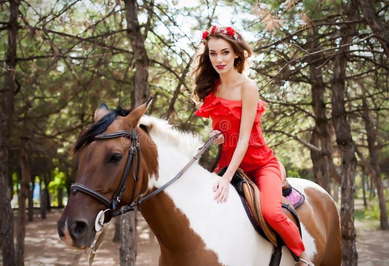 Schöne junge Dame, die das rote Kleid reitet ein Pferd am sonnigen Sommertag trägt Brunette mit dem langen gelockten Haar mit Blu lizenzfreie stockfotografie