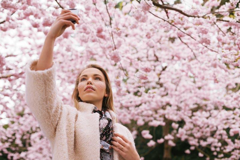Schöne junge Dame, die Natur mit ihrem Handy fotografiert stockbild