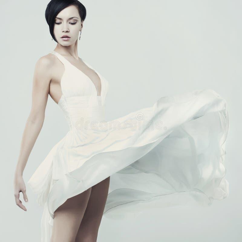 Schöne junge Dame in einem türmenden weißen Kleid lizenzfreie stockfotografie