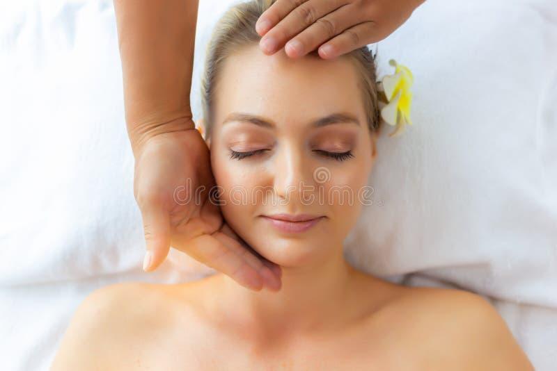 Schöne junge Dame glauben Entspannung, Glück und Entlastung vom Druck wenn Massagermassage auf ihrem schönen Gesicht am Badekuror lizenzfreies stockbild