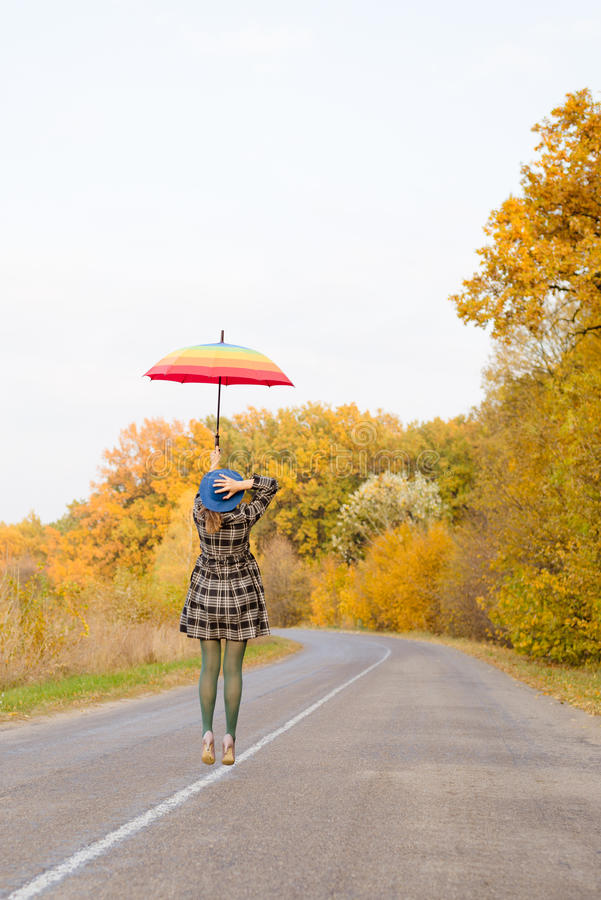 Schöne junge Dame mit dem Regenschirm, der an springt stockbild