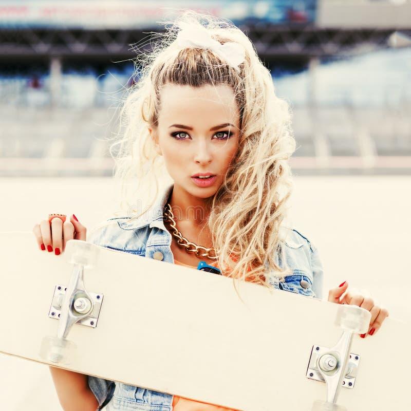 Schöne junge Dame mit einem Skateboard mit leerer Plattform stockfotografie