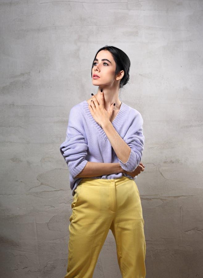 Schöne junge denkende Frau, die oben mit der Hand auf dem Hals in der violetten Strickjacke, gelbe Hosen auf grauem Studio aufwir stockbild