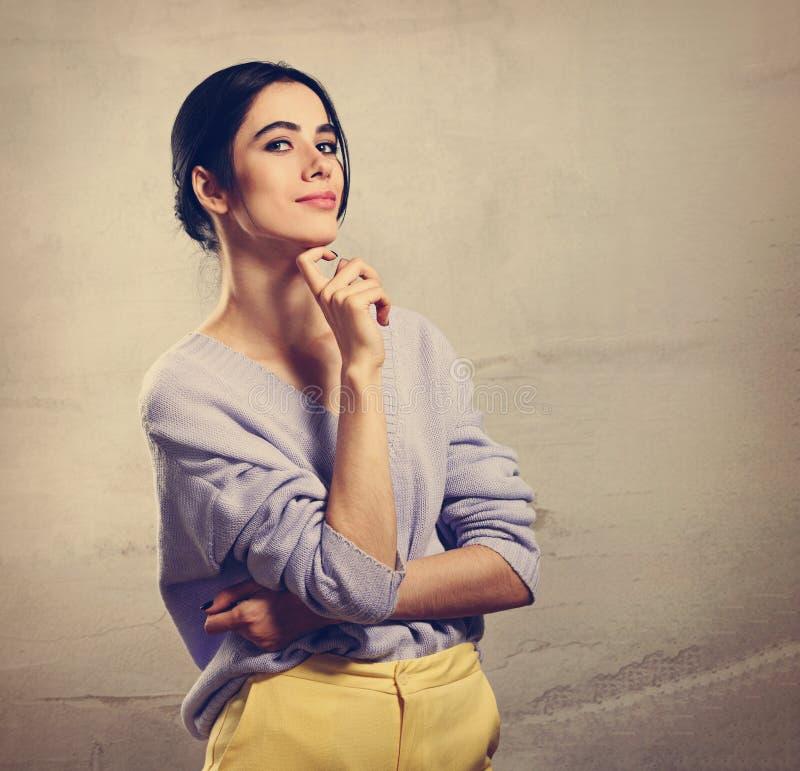 Schöne junge denkende Frau, die oben mit der Hand unter dem Gesicht in der violetten Strickjacke und in den gelben Hosen auf grau stockfoto