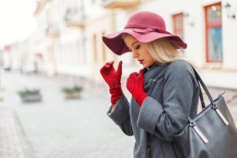 Schöne junge elegante Frau in einem modischen Hut und in einem grauen Mantel lizenzfreies stockfoto
