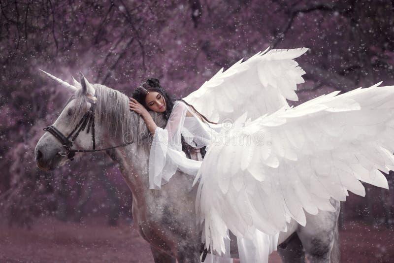Schöne, junge Elfe, gehend mit einem Einhorn Sie trägt ein unglaubliches Licht, weißes Kleid Kunst hotography lizenzfreie stockfotos
