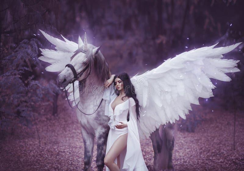 Schöne, junge Elfe, gehend mit einem Einhorn Sie trägt ein unglaubliches Licht, weißes Kleid Kunst hotography lizenzfreie stockfotografie