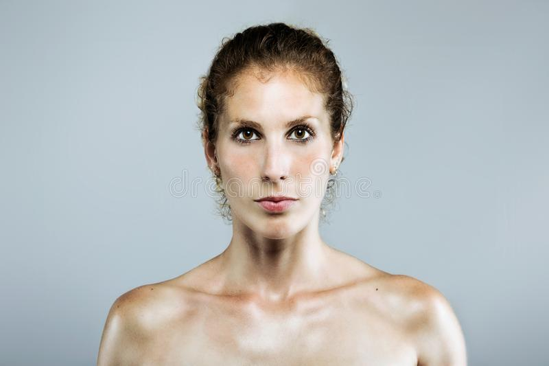Schöne junge ernste Frau, die Kamera über grauem Hintergrund betrachtet lizenzfreies stockfoto