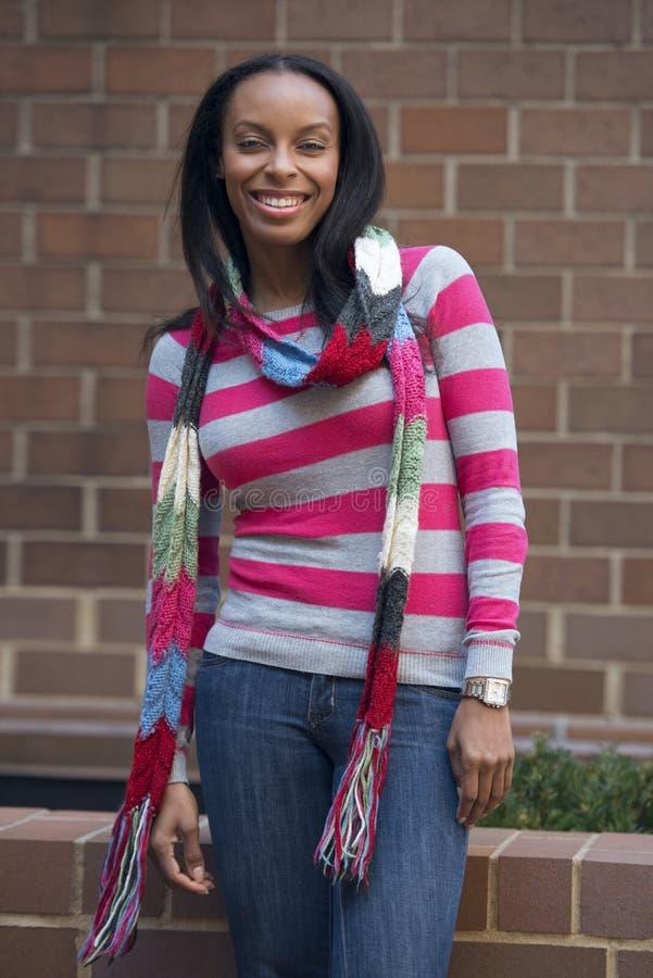 Schöne junge erwachsene Afroamerikanerfrau, die draußen gegen tragenden Schal der Backsteinmauer, bunte Herbststrickjacke aufwirf stockbild