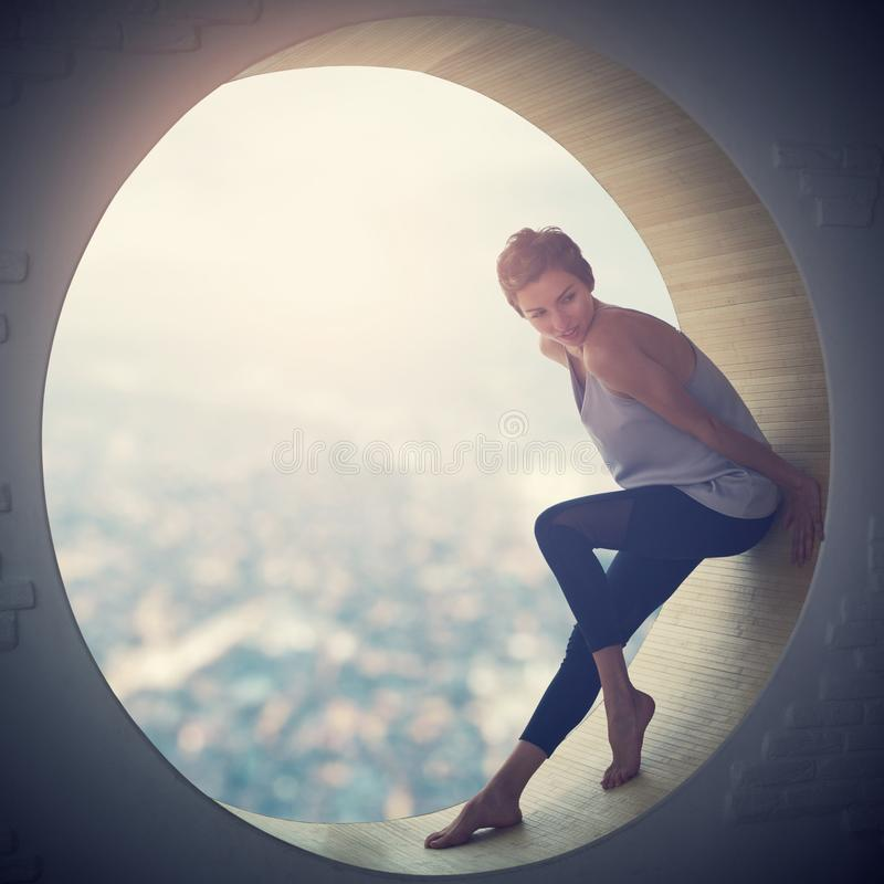 Schöne junge erwachsene dünne hübsche und attraktive Sinnlichkeitsfrau in der Eleganzmodischen kleidung in einem runden Fenster stockbilder