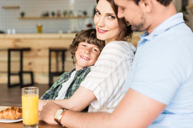 schöne junge Familie mit wenig gelocktem Kinderabbinden lizenzfreie stockfotos