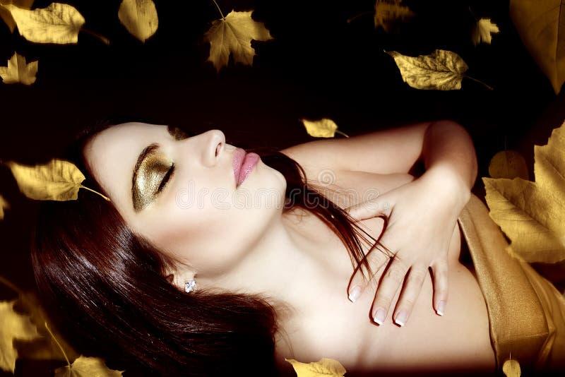 Schöne junge Frau über Herbsthintergrund lizenzfreie stockfotos