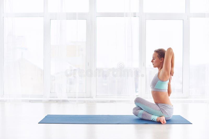 Schöne junge Frau übt Yoga asana Garudasana - Eagle-Haltung am Yogastudio stockbild