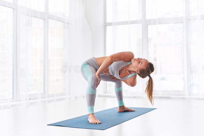 Schöne junge Frau übt Yoga asana Parivritta Stupasana an der Yogaklasse lizenzfreie stockfotografie