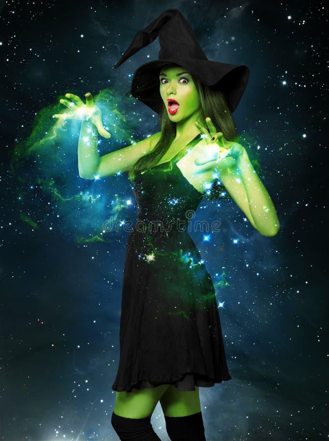 Schöne junge Frau als Halloween-Hexe lizenzfreie stockfotos