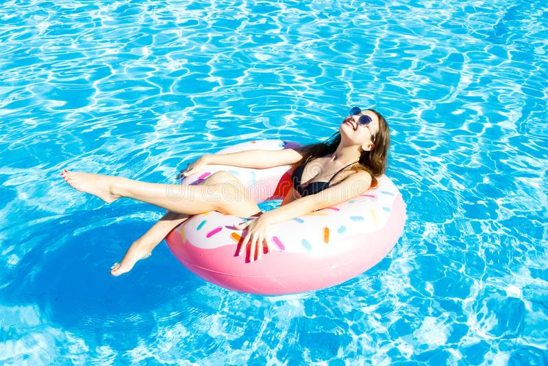 Schöne junge Frau auf aufblasbarem Donut im Swimmingpool stockbild