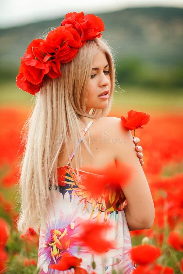 Schöne junge Frau auf dem Mohnblumengebiet des roten Lichtes stockfoto