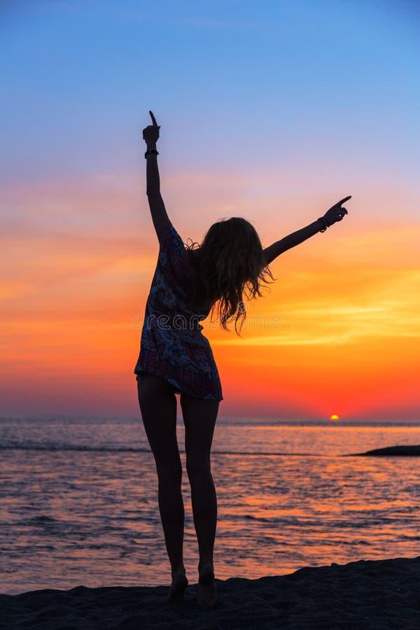 Schöne junge Frau auf dem Strand bei Sonnenuntergang stockbilder