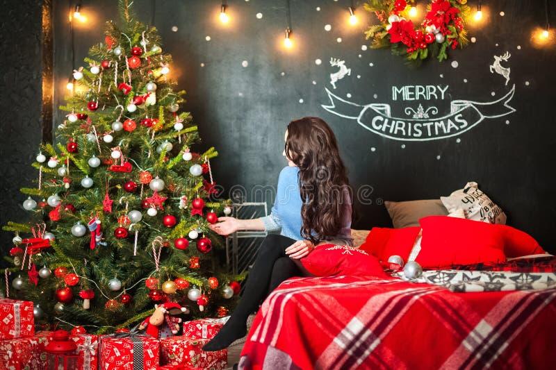 Schöne junge Frau auf einem Bett verziert einen Baum des neuen Jahres Brunette im Schlafzimmer für Weihnachten stockfotografie