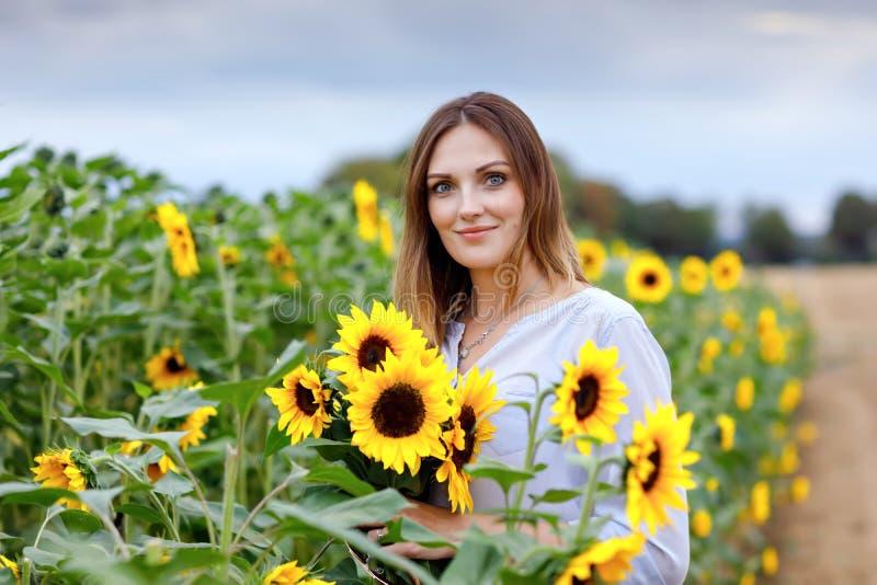 Schöne junge Frau auf Sonnenblumenfeld mit Blumenstrauß blüht Glückliches Mädchen am Sommersonnenuntergangtag lizenzfreie stockfotografie