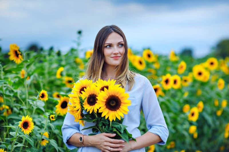 Schöne junge Frau auf Sonnenblumenfeld mit Blumenstrauß blüht Glückliches Mädchen am Sommersonnenuntergangtag lizenzfreies stockbild