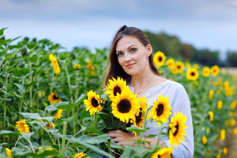 Schöne junge Frau auf Sonnenblumenfeld mit Blumenstrauß blüht Glückliches Mädchen am Sommersonnenuntergangtag stockfotos