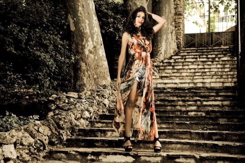 Schöne junge Frau, Baumuster der Mode, in den Treppen eines Gartens lizenzfreie stockbilder
