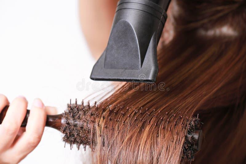 Schöne junge Frau benutzt einen Haartrockner lizenzfreies stockfoto