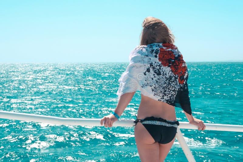 Schöne junge Frau betrachtet das Meer am Sommertag Ansicht von der Rückseite lizenzfreie stockfotografie