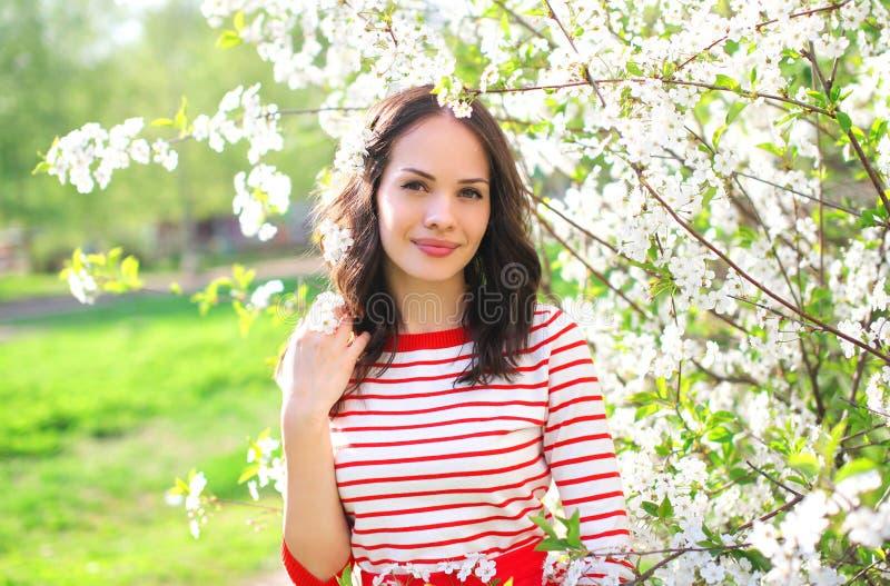 Schöne junge Frau in blühendem Frühlingsgarten stockfotografie