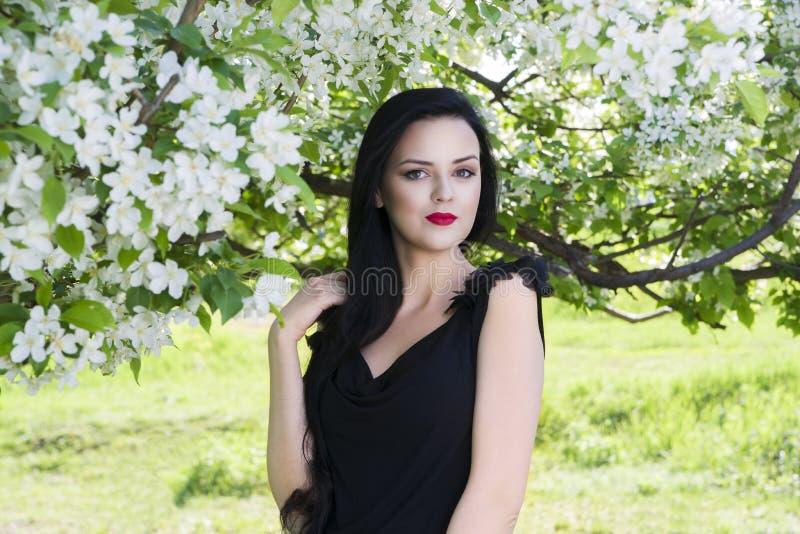Schöne junge Frau in blühendem Frühlingsgarten mit weißen Blumen, Berufsmake-up stockfotografie