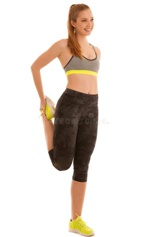 Schöne junge Frau dehnt das Bein aus, das über weißem backgrou lokalisiert wird lizenzfreie stockbilder
