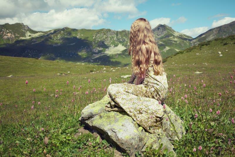 Schöne junge Frau in den Bergen auf einer Wiese stockfoto
