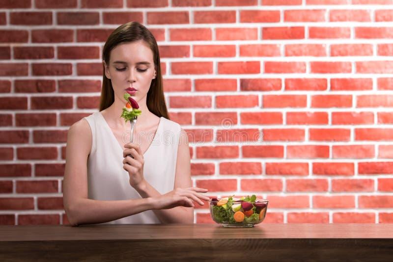 Schöne junge Frau in den frohen Lagen mit der Hand, die Salat hält lizenzfreies stockfoto