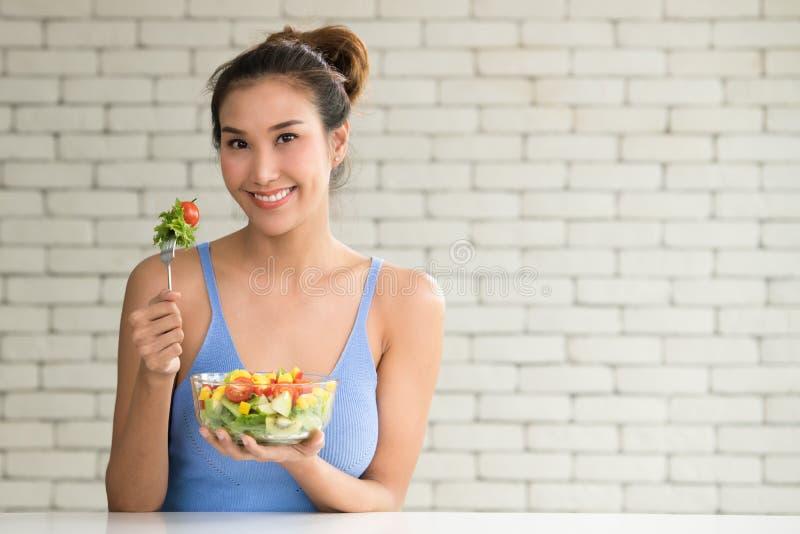Schöne junge Frau in den frohen Lagen mit der Hand, die Salat hält stockbilder