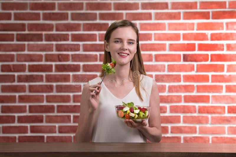 Schöne junge Frau in den frohen Lagen mit der Hand, die Salatschüssel hält lizenzfreie stockfotografie