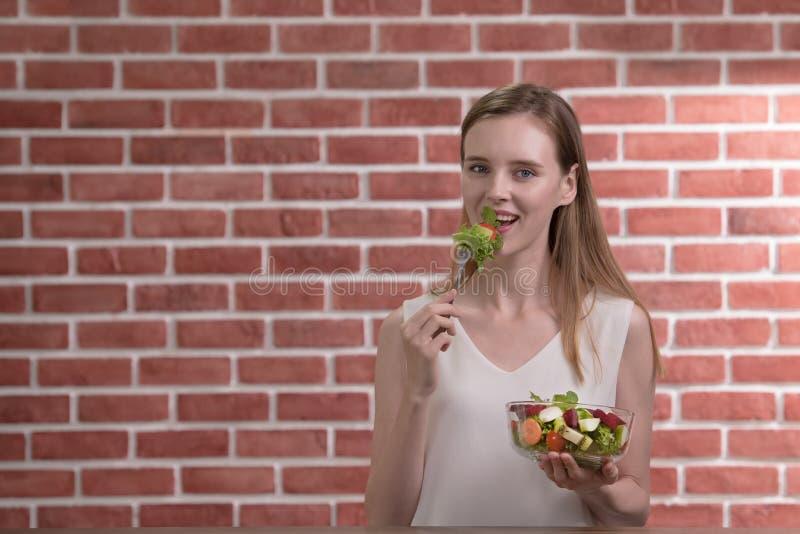 Schöne junge Frau in den frohen Lagen mit der Hand, die Salatschüssel hält lizenzfreie stockfotos
