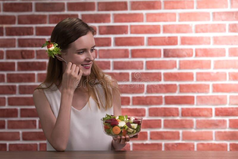 Schöne junge Frau in den frohen Lagen mit der Hand, die Salatschüssel hält stockbild