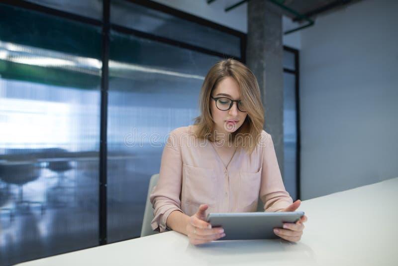 Schöne junge Frau in den Gläsern, die am Schreibtisch im Büro sitzen und eine Tablette verwenden Betrachten Sie die Tablette lizenzfreies stockbild