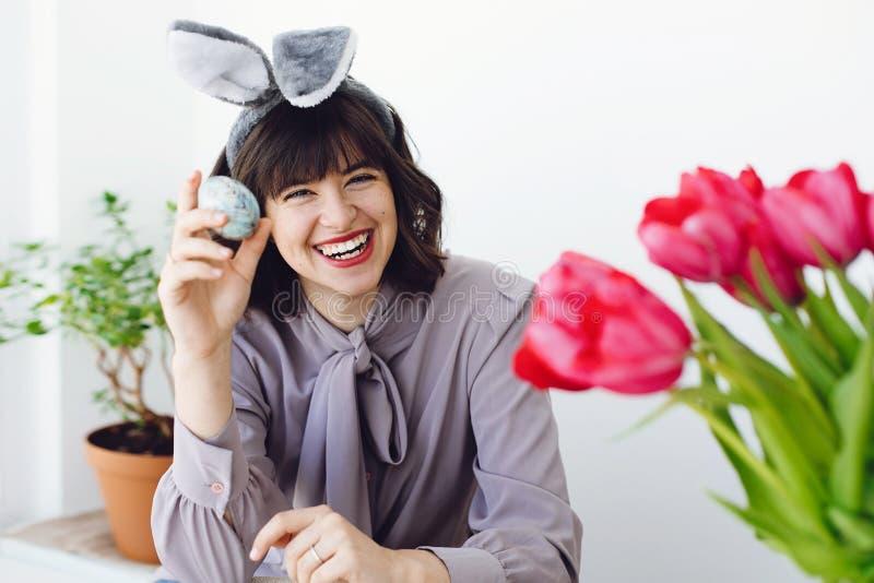 Schöne junge Frau in den Häschenohren, die Osterei malen und bei Tisch mit Farbe, Bürsten, Tulpen im Vase lächeln Glückliches Mäd stockfoto