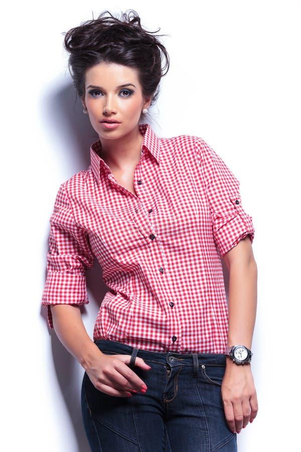 Schöne junge Frau in den Jeans und im roten Hemd stockfoto