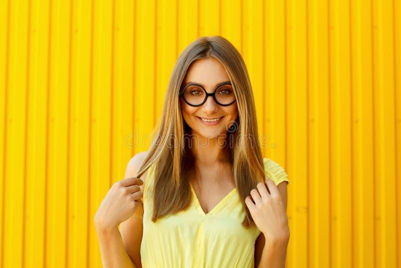 Schöne junge Frau in den lustigen Spielzeuggläsern lächelnd über gelbem b stockfotografie